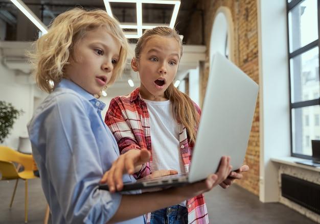 Dwoje ciekawskich dzieci, mały chłopiec i dziewczynka wygląda na zaskoczonych podczas korzystania z laptopa stojącego w klasie