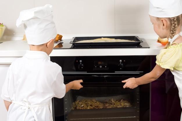 Dwoje dumnych małych dzieci wkładających pizzę do piekarnika