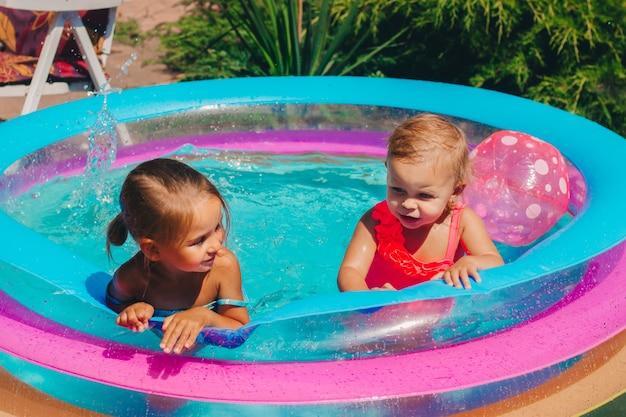 Dwoje dzieci bawi się w nadmuchiwanym basenie