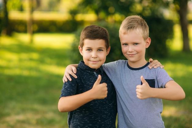 Dwoje dzieci bawi się w parku. dwóch pięknych chłopców w koszulkach i szortach bawi się z uśmiechem. jedzą lody, skaczą, biegają. lato jest słoneczne.