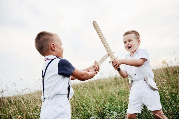 Dwoje dzieci, bawiąc się drewnianymi mieczami w polu.