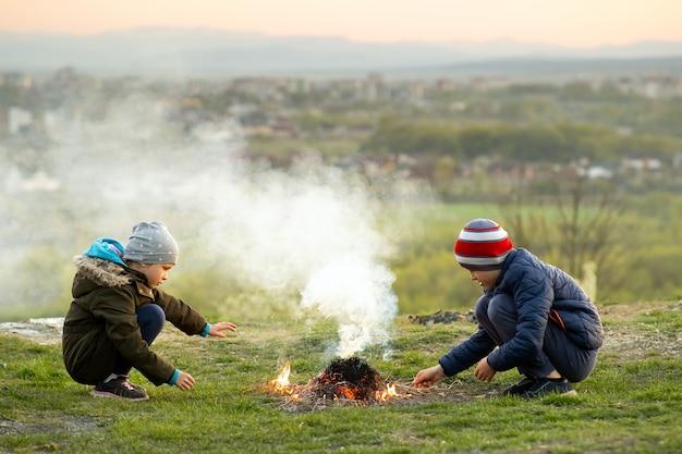 Dwoje dzieci bawiące się ogniem na zewnątrz w chłodne dni.