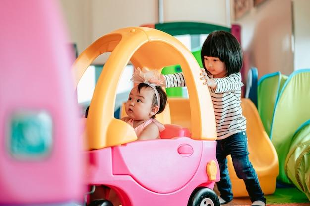 Dwoje dzieci bawiło się razem bawiąc się końmi na biegunachrodzina z dziećmi w domu miłość