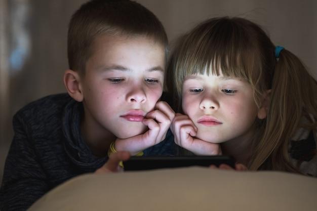 Dwoje dzieci brat i siostra oglądają razem wideo na ekranie telefonu.