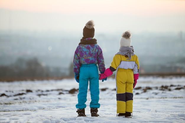 Dwoje dzieci, brat i siostra, stojących na zewnątrz na śniegu pokryte zimą pole trzymając się za ręce.