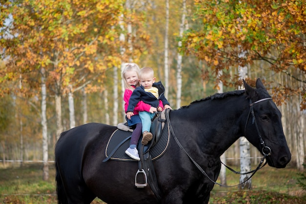 Dwoje dzieci, chłopiec i dziewczynka na czarnym koniu, ma radosne emocje