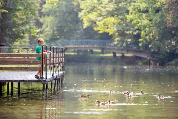 Dwoje dzieci chłopiec i dziewczynka stojąc na drewnianym pokładzie na brzegu jeziora karmienia kaczek