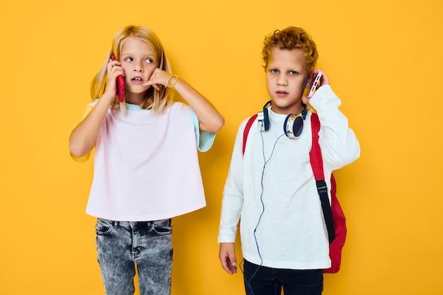 Dwoje dzieci, chłopiec i dziewczynka, używają gadżetów ze słuchawkami na białym tle