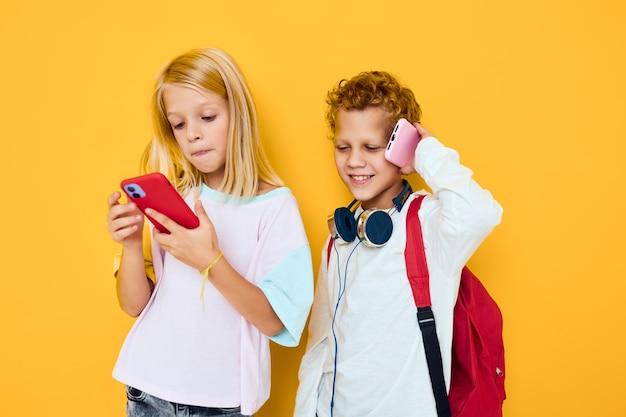 Dwoje dzieci chłopiec i dziewczynka używają gadżetów ze słuchawkami na żółtym tle. zdjęcie wysokiej jakości