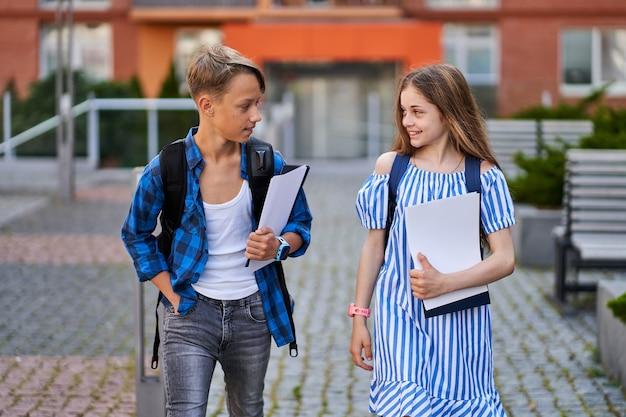 Dwoje dzieci chłopiec i dziewczynka z książkami plecaki idzie do szkoły.