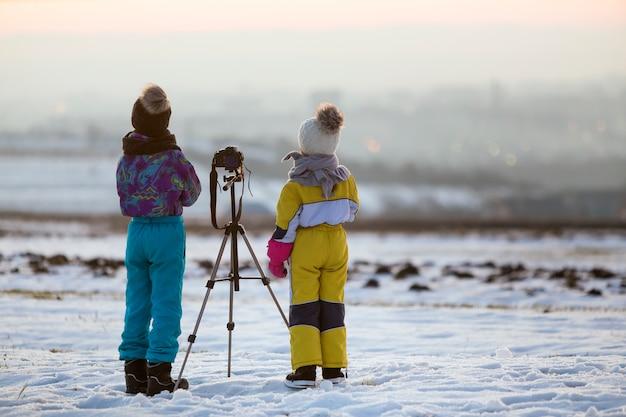 Dwoje dzieci chłopiec i dziewczynka zabawy poza zimą, grając z aparatu fotograficznego na statywie na pokryte śniegiem pole.