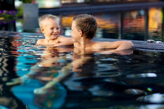 Dwoje dzieci cieszących się dniem na basenie?