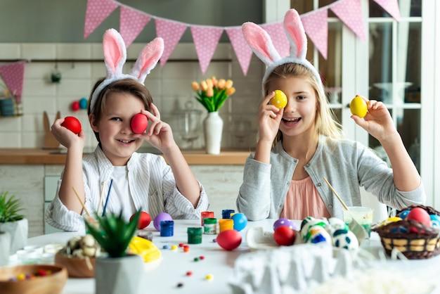 Dwoje dzieci dobrze się bawi, zamykając oczy wielkanocnym jajkiem.