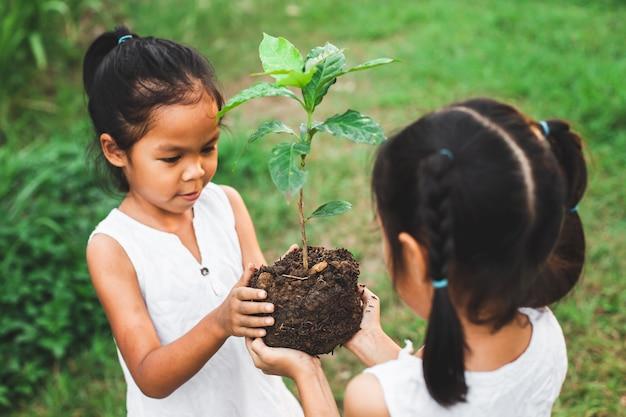 Dwoje dzieci dziewczyna trzyma młode drzewo do sadzenia razem jako save world concept