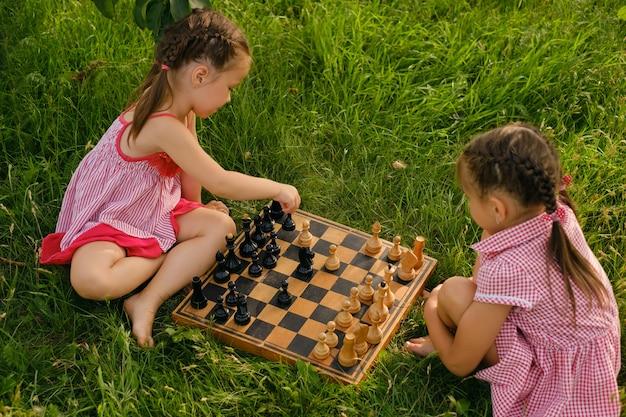 Dwoje dzieci gra w szachy w ogrodzie na trawie na świeżym powietrzu