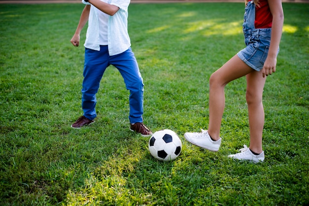 Dwoje dzieci grających w piłkę nożną na trawie
