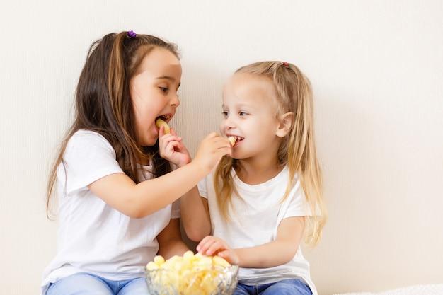 Dwoje dzieci jedzą popcorn na białym tle