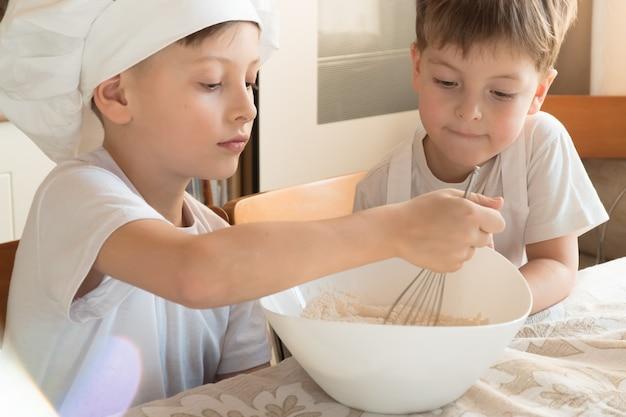 Dwoje dzieci kaukaskich chłopców gotuje w kuchni w domu?