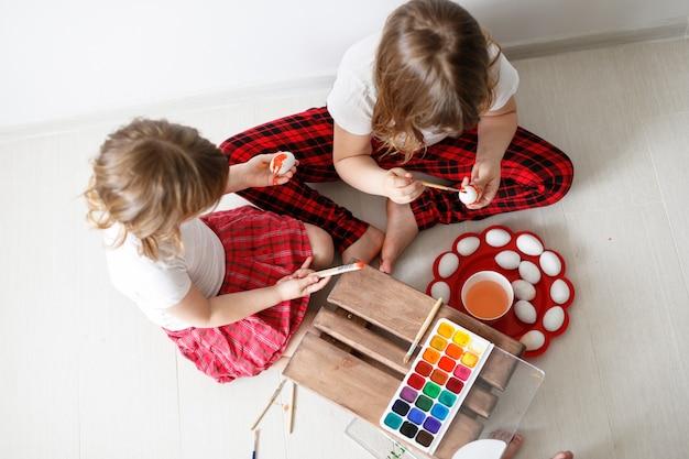 Dwoje dzieci maluje jajka akwarelami, wielkanoc