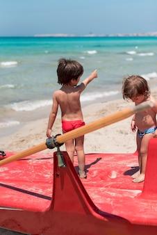 Dwoje dzieci na plaży stoi na łodzi wiosła