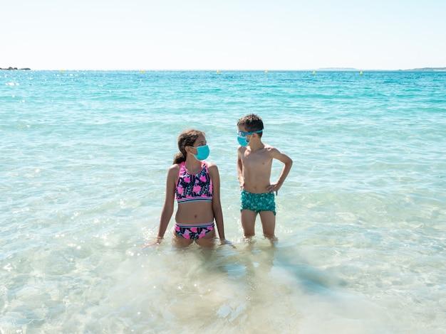 Dwoje dzieci na plaży w maskach ochronnych, aby zapobiec chorobie koronawirusa