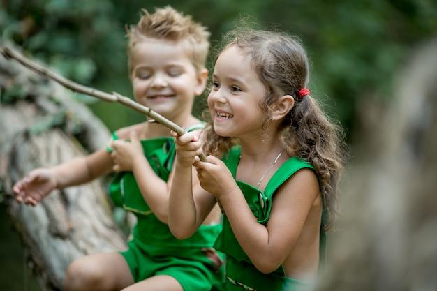 Dwoje dzieci na zewnątrz, brat i siostra w zielonych garniturach, spacery po lesie w pobliżu jeziora