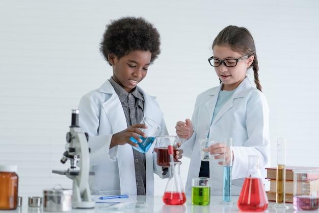 Dwoje dzieci naukowców przeprowadzających eksperymenty chemiczne w sali laboratoryjnej w szkole.