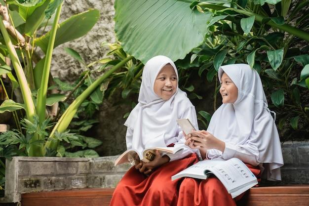 Dwoje dzieci noszących zasłonę w mundurkach szkolnych korzysta ze smartfona podczas rozmowy i nauki