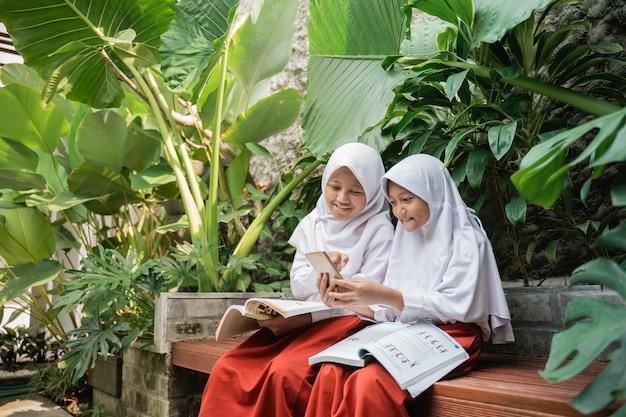Dwoje dzieci noszących zasłonę w mundurkach szkolnych korzystających z telefonu komórkowego i książki podczas wspólnej nauki