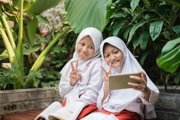 Dwoje dzieci noszących zasłonę w mundurkach szkolnych używa razem smartfona podczas nauki