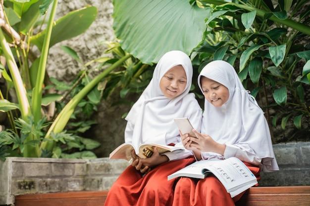 Dwoje dzieci noszących zasłonę w mundurkach szkolnych używa smartfona podczas nauki
