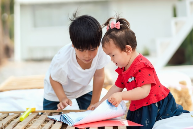 Dwoje dzieci otwiera książkę do nauki
