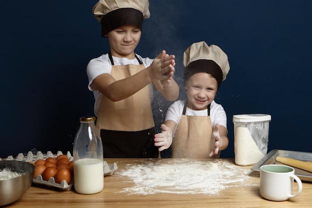 Dwoje dzieci płci męskiej przygotowujących ciasto, podczas gdy z powrotem wraca biszkopt lub ciasteczka dla matki w jej urodziny. śliczne szczęśliwe chłopcy pozują we wnętrzu nowoczesnej kuchni z rękami w mące, gotowanie chleba