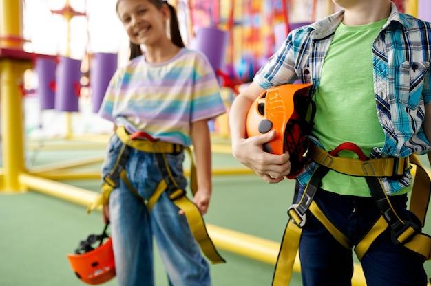 Dwoje dzieci pozuje na terenie wspinaczkowym, młody wspinacz