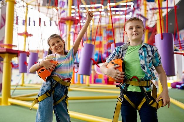 Dwoje dzieci pozuje w strefie wspinaczkowej w centrum rozrywki, młodzi wspinacze. chłopiec i dziewczynka bawią się na linach, dzieciaki spędzają weekend na placu zabaw, szczęśliwe dzieciństwo