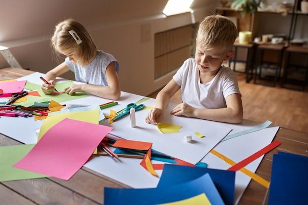 Dwoje dzieci pracuje z kolorowym papierem przy stole, dzieci w warsztacie. lekcja kreatywności w szkole artystycznej. młodzi malarze, przyjemne hobby, szczęśliwe dzieciństwo