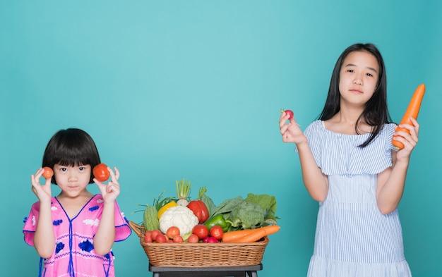 Dwoje dzieci przewożących warzywa na niebieskim tle