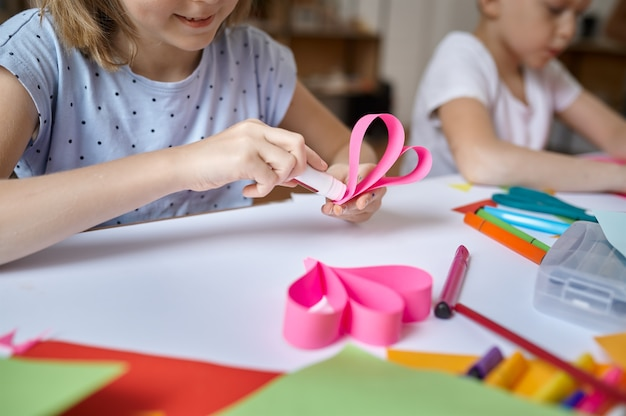Dwoje dzieci przykleja kolorowy papier przy stole, dzieci w warsztacie. lekcja kreatywności w szkole artystycznej. młodzi malarze, przyjemne hobby, szczęśliwe dzieciństwo