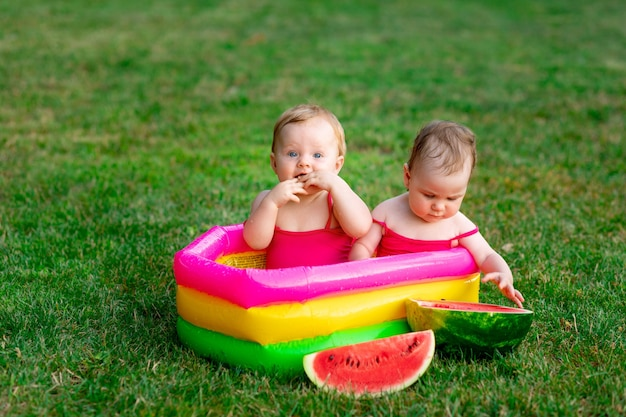 Dwoje dzieci radosnych bliźniaków pływa latem w nadmuchiwanym basenie na zielonej trawie z arbuzem, miejsce na tekst