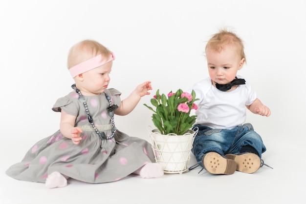 Dwoje dzieci siedzących na białej przestrzeni z kwiatami