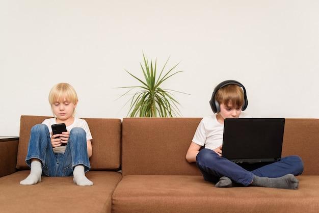Dwoje dzieci siedzących na kanapie z gadżetami smartphone i laptop. generacja alfa.