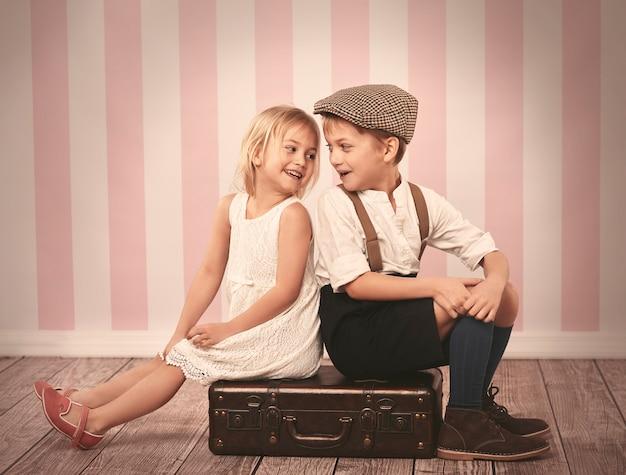 Dwoje dzieci siedzi na drewnianej walizce