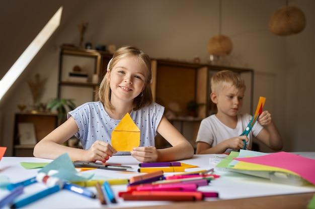 Dwoje dzieci tnie kolorowy papier przy stole, dzieci w warsztacie. lekcja kreatywności w szkole artystycznej. młodzi malarze, przyjemne hobby, szczęśliwe dzieciństwo