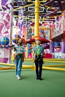 Dwoje dzieci w hełmach wspina się na linie zip w centrum rozrywki, młodzi wspinacze, widok z przodu. chłopiec i dziewczynka bawią się na linach w strefie wspinaczkowej, dzieci spędzają weekend na placu zabaw, szczęśliwe dzieciństwo
