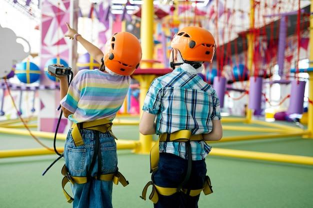 Dwoje dzieci w hełmach wspina się na linię zip w centrum rozrywki, młodzi wspinacze, widok z tyłu. chłopiec i dziewczynka bawią się na linach w strefie wspinaczkowej, dzieci spędzają weekend na placu zabaw, szczęśliwe dzieciństwo