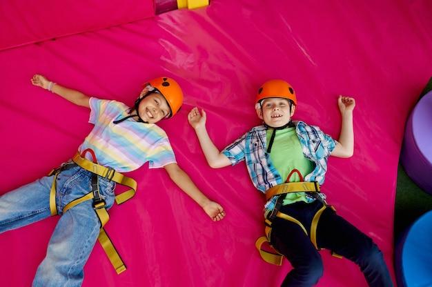 Dwoje dzieci w kaskach leżących na matach przy ściance wspinaczkowej w centrum rozrywki, młodzi wspinacze. chłopiec i dziewczynka bawią się na linach, dzieciaki spędzają weekend na placu zabaw, szczęśliwe dzieciństwo