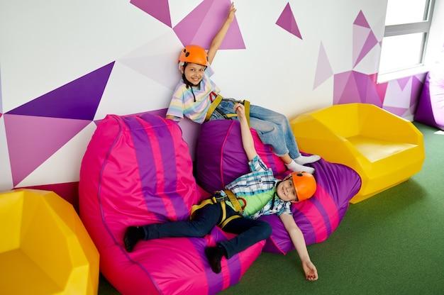 Dwoje dzieci w kaskach odpoczywających w strefie wspinaczkowej w centrum rozrywki, młodzi wspinacze. chłopiec i dziewczynka bawią się na linach, dzieciaki spędzają weekend na placu zabaw, szczęśliwe dzieciństwo