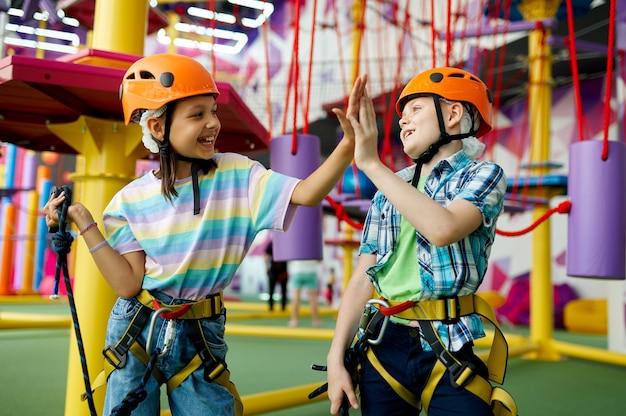 Dwoje dzieci w kaskach wspina się na tyrolkę w centrum rozrywki, młodzi wspinacze. chłopiec i dziewczynka bawią się na linach w strefie wspinaczkowej, dzieci spędzają weekend na placu zabaw, szczęśliwe dzieciństwo