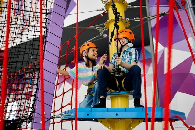 Dwoje dzieci w kaskach wspina się po linie w centrum rozrywki. chłopiec i dziewczynka bawią się na linach w strefie wspinaczkowej, dzieci spędzają weekend na placu zabaw, szczęśliwe dzieciństwo