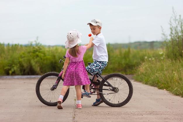 Dwoje dzieci w letni dzień rower i kwiat chłopiec i dziewczynka